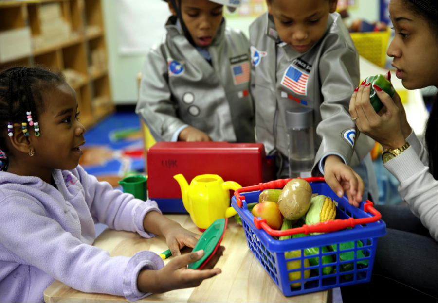 Oumou Balde, 4, with her teacher,  Jacqueline Sanchez, in a nutrition program in New York. (courtesy of Seth Wenig/Associated Press)